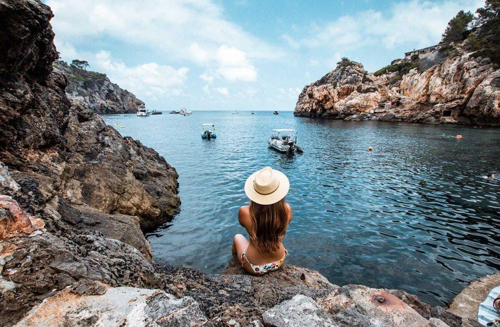 Melissa sitting on a rock at Cala Deia in Mallorca