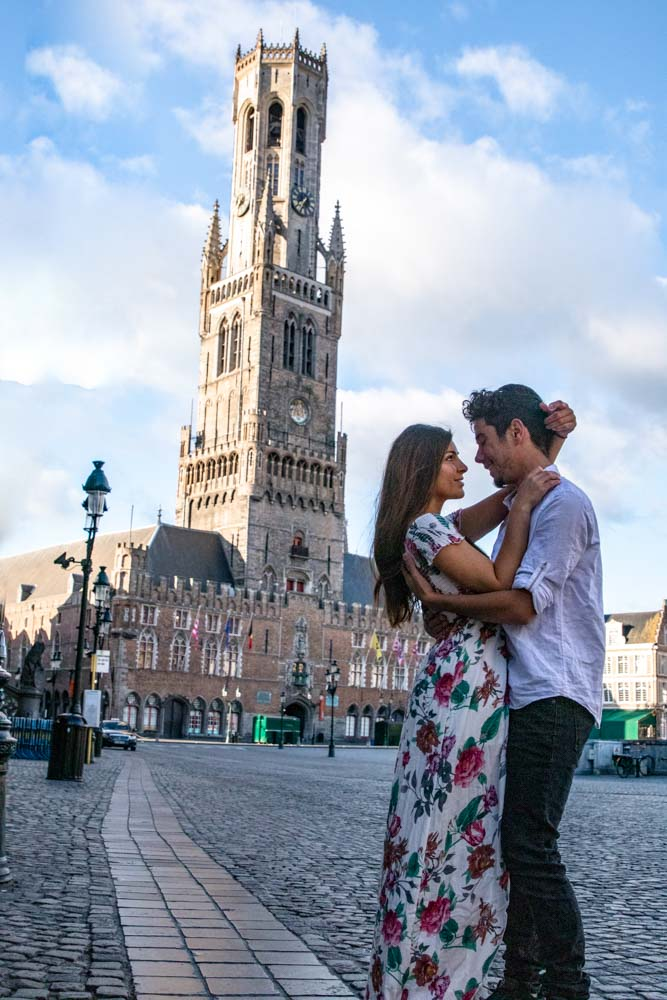 Melissa and Guga looking at each other in front of the Bruges Belfry