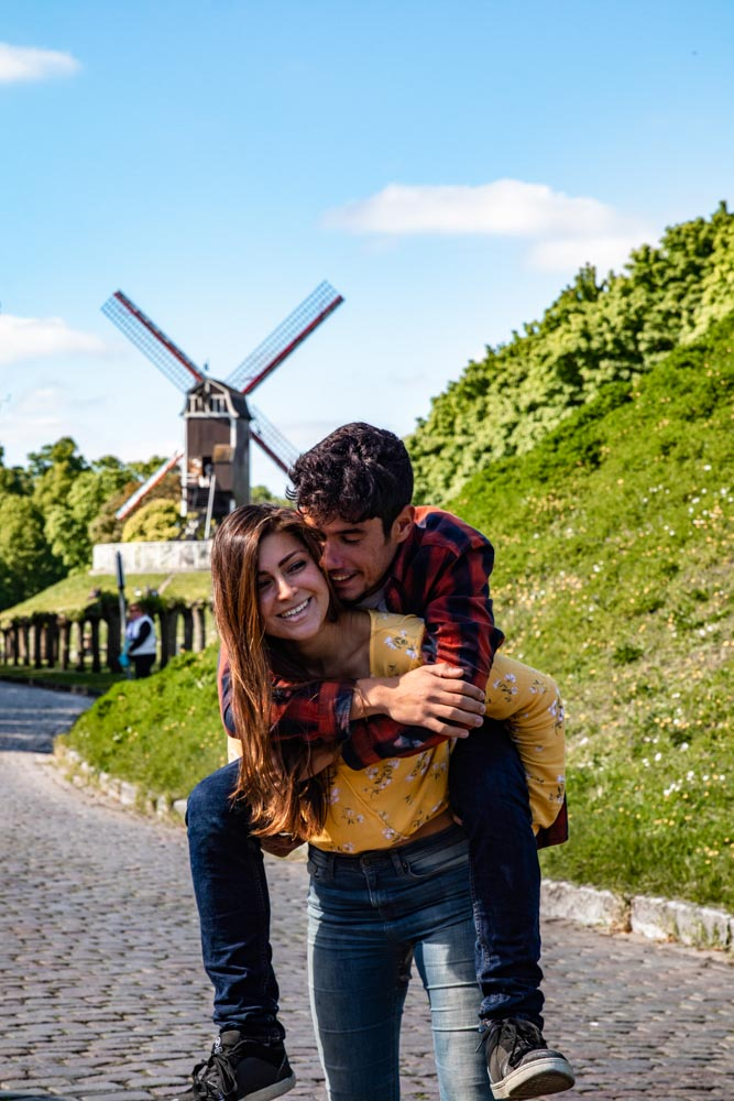 Guga on Melissa's piggyback with Bruges' windmills in the background