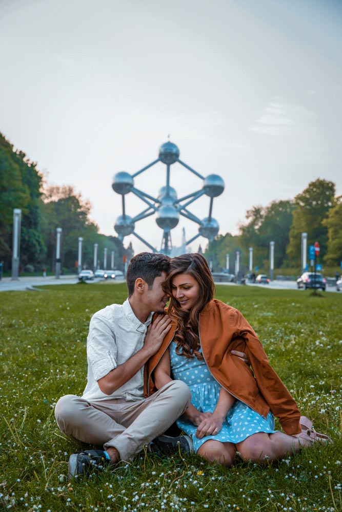 Melissa and Guga sitting on the grass in front of the Atomium in Brussels