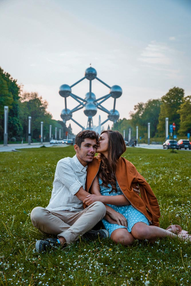 Melissa kissing guga on the forehead sitting on the grass in front of the Atomium with the Atomium in the background