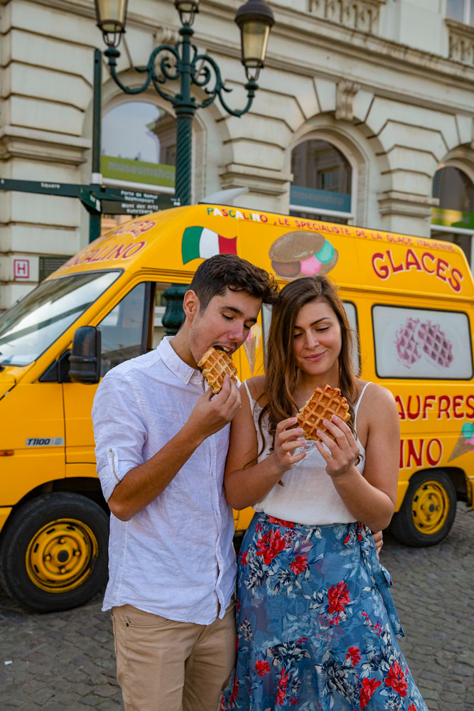 Melissa and Guga eating waffles next to a yellow waffles van in Brussels