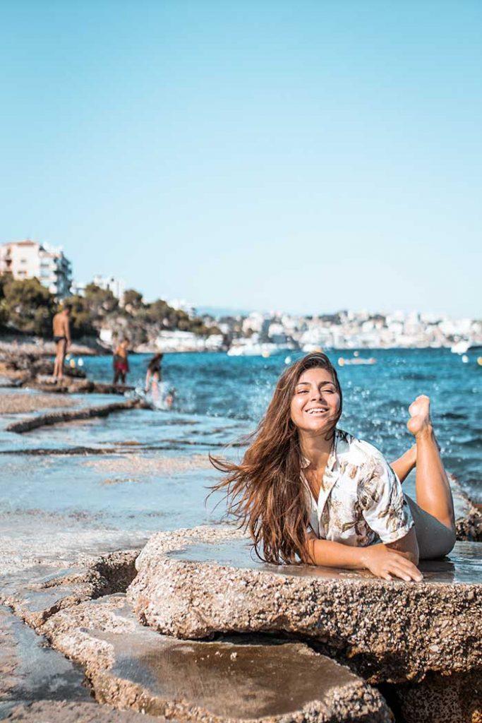 Melissa lying down on a rock at Cala Comtesa in Mallorca
