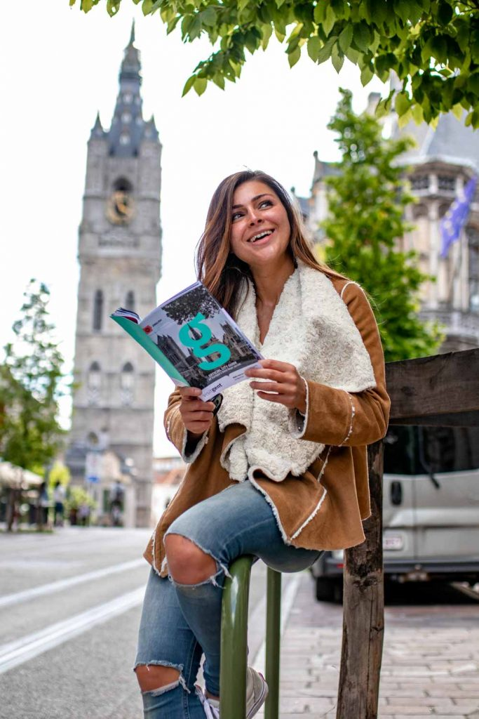 Melissa reading the Ghent magazine standing next to the ghent belfry