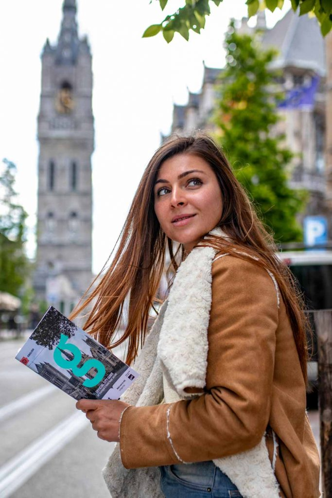 Melissa looking over her shoulder holding the Ghent magazine in front of the Ghent Belfry
