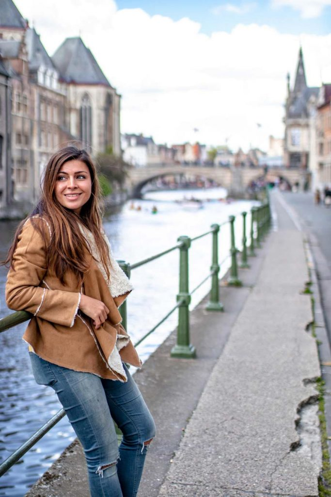 Melissa leaning on an iron bar next to the river of Ghent