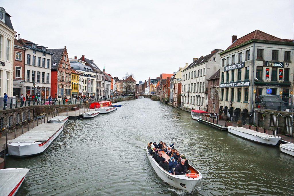 photo from above the canal of Ghent showing a crowd having a boat tour in ghent