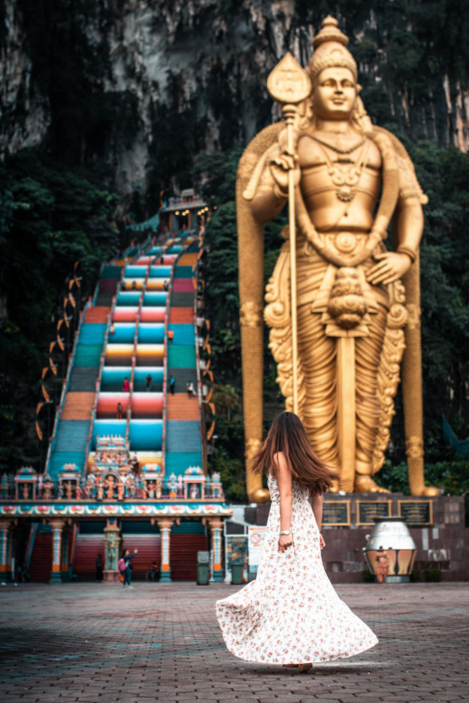 Melissa swishes her skirt at the entrance to the rainbow steps of the Batu Caves in Malaysia.