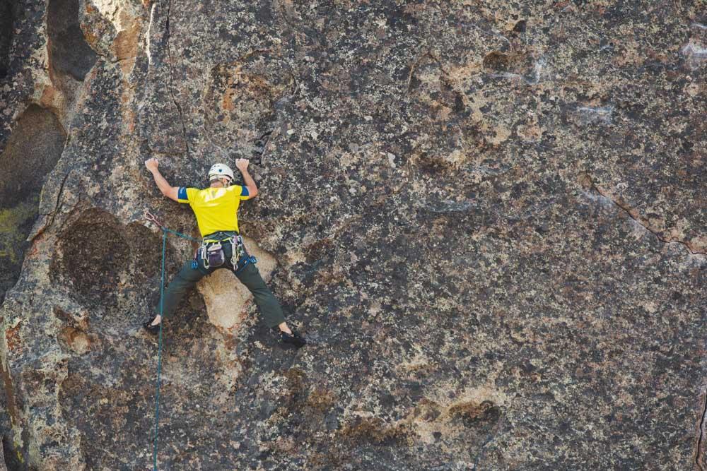 A man in a yellow shirt is rock climbing a steep wall.