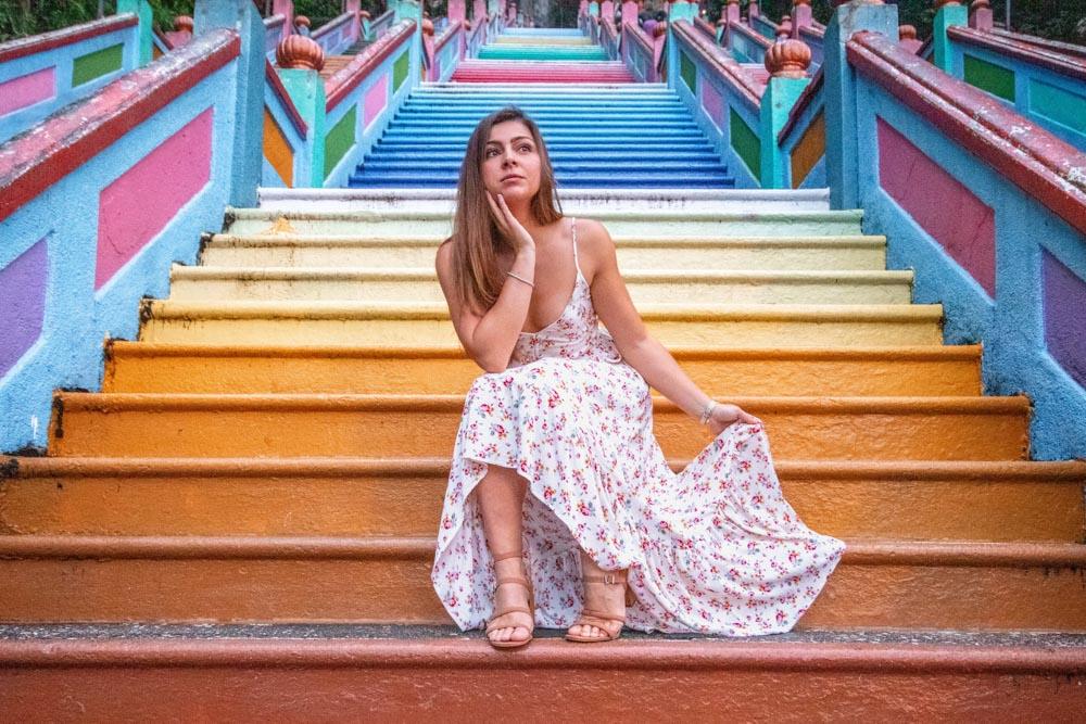 Melissa sits on the rainbow steps of the Batu Caves in Kuala Lumpur.