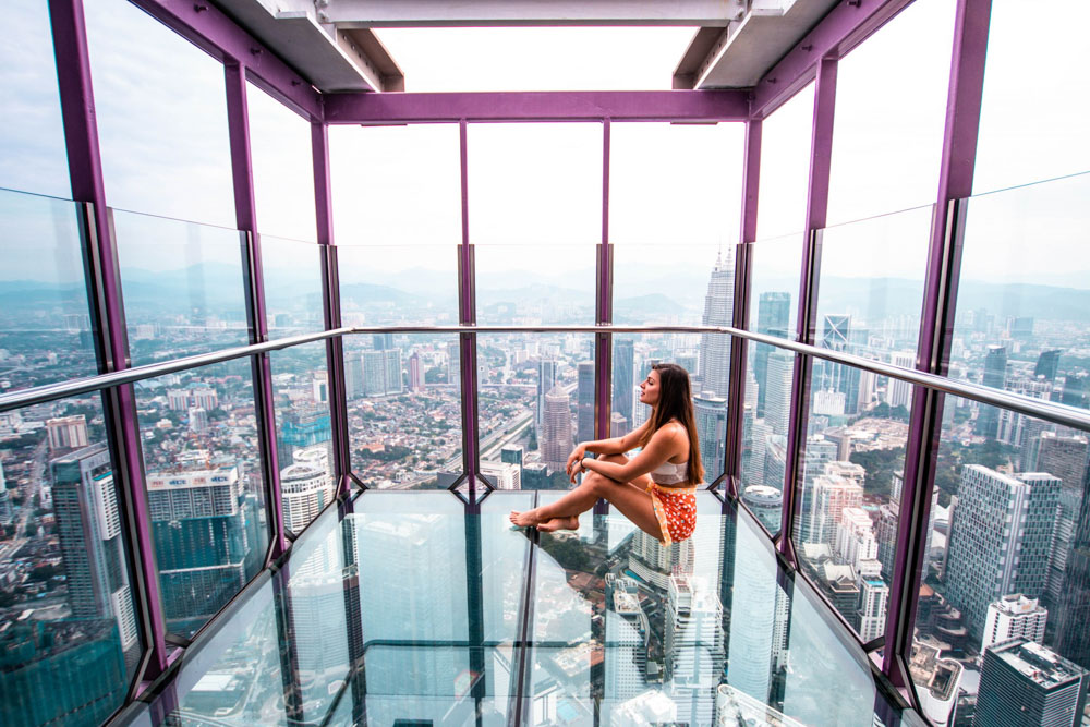 Melissa sits in the glass Sky Box KL Tower in Kuala Lumpur