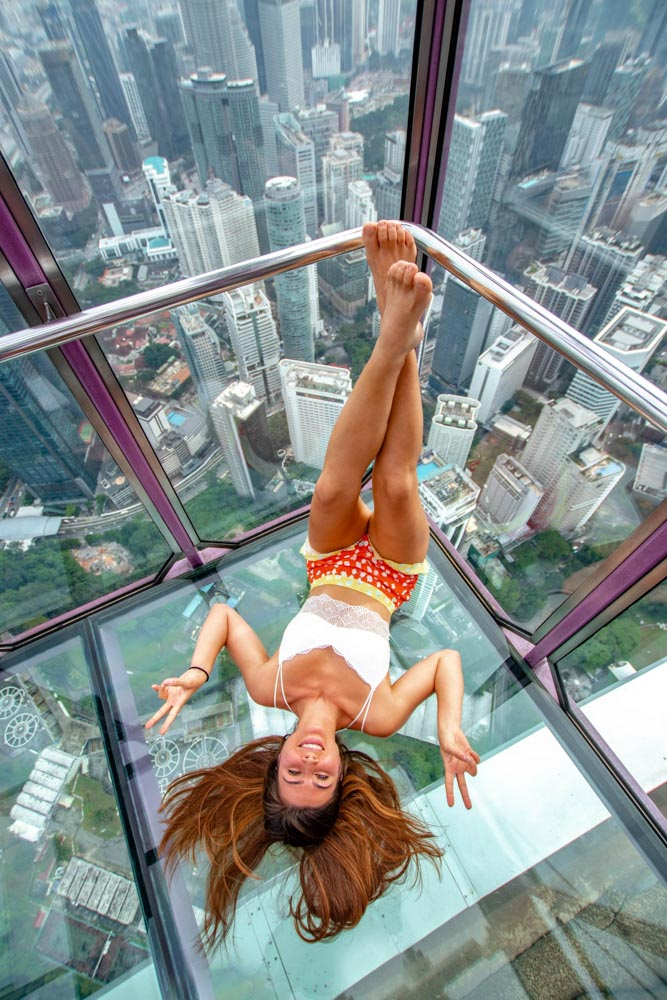 Melissa sitting upside down in the Sky Box at KL Tower in Kuala Lumpur