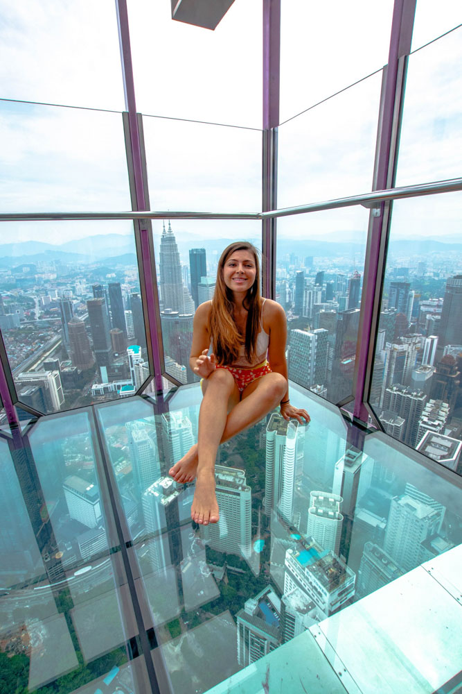 Melissa sits in the glass sky box in the KL tower, smiling.