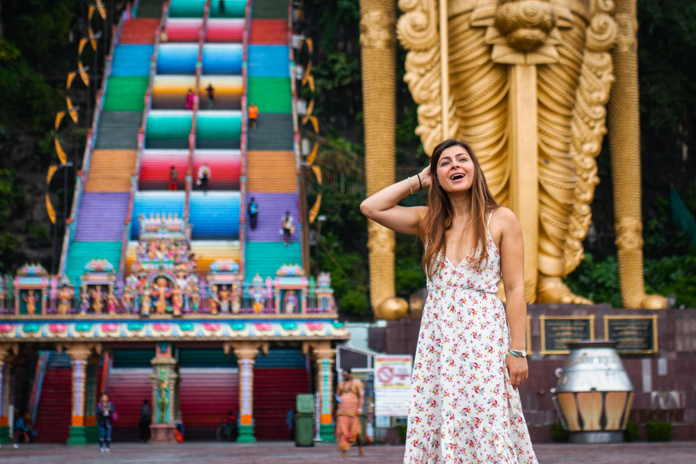Melissa smiling with the golden statue and the rainbow stairs at the Batu Caves behind her