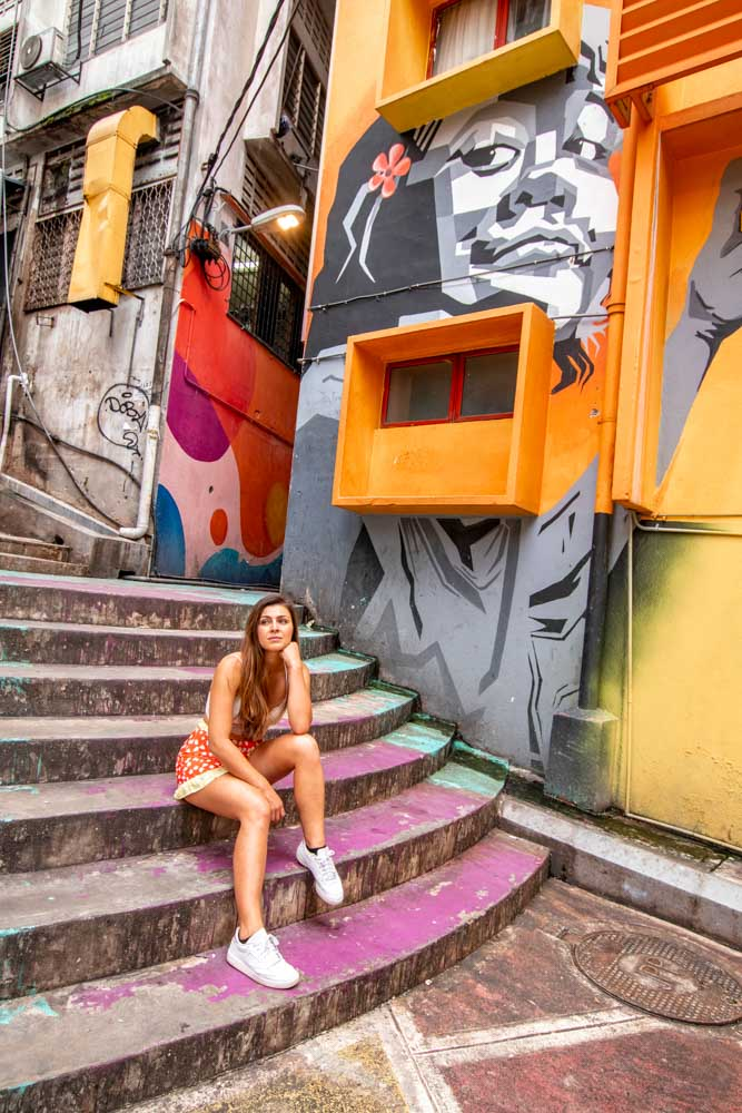 Melissa sits on the stairs of the colourful graffiti streets of Bukit Bintang in KL.