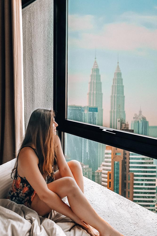 Melissa sits in her hotel bed, looking out the window at the Petronas Towers in KL.