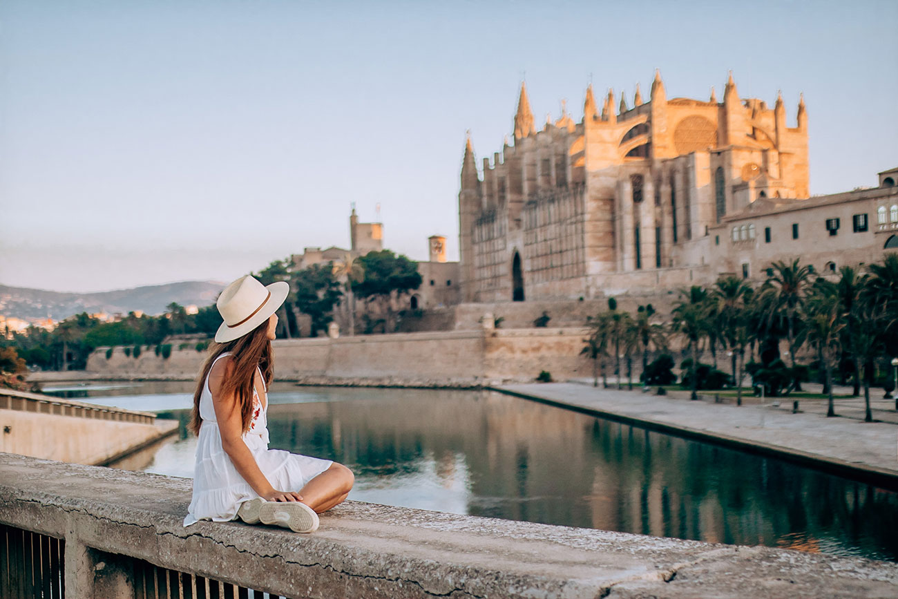 Melissa sitting in front of Parc de La Mar with La Seu Cathedral in the background