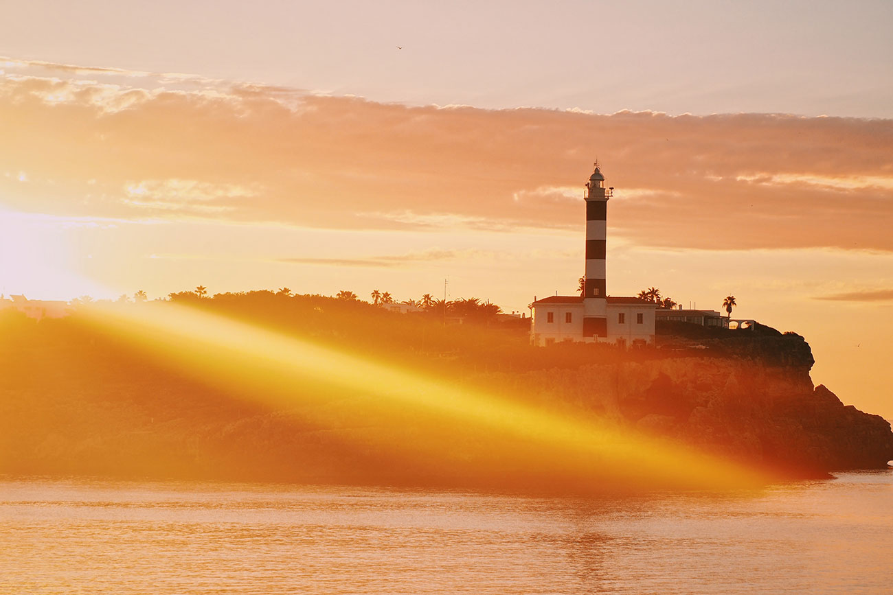 sunset at Portocolom with a view of the lighthouse