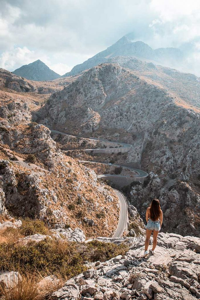 Melissa standing on a rock with the winding roads of Sa Calobra in the background