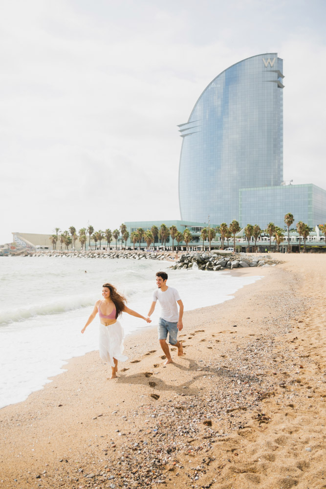 Guga and Girl Around the World holding hands in Barceloneta Beach with W Barcelona in the background