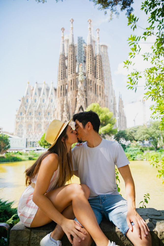 Melissa and Guga kissing under a tree with La Sagrada Familia in the background
