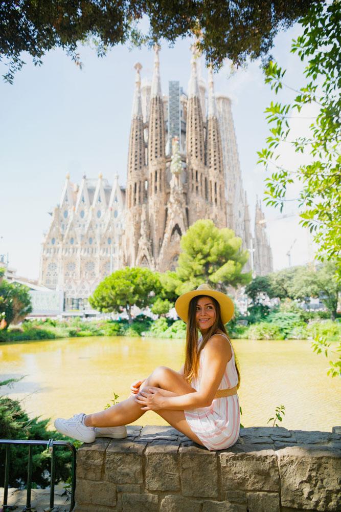 Melissa sitting under a tree with La Sagrada Familia in the background