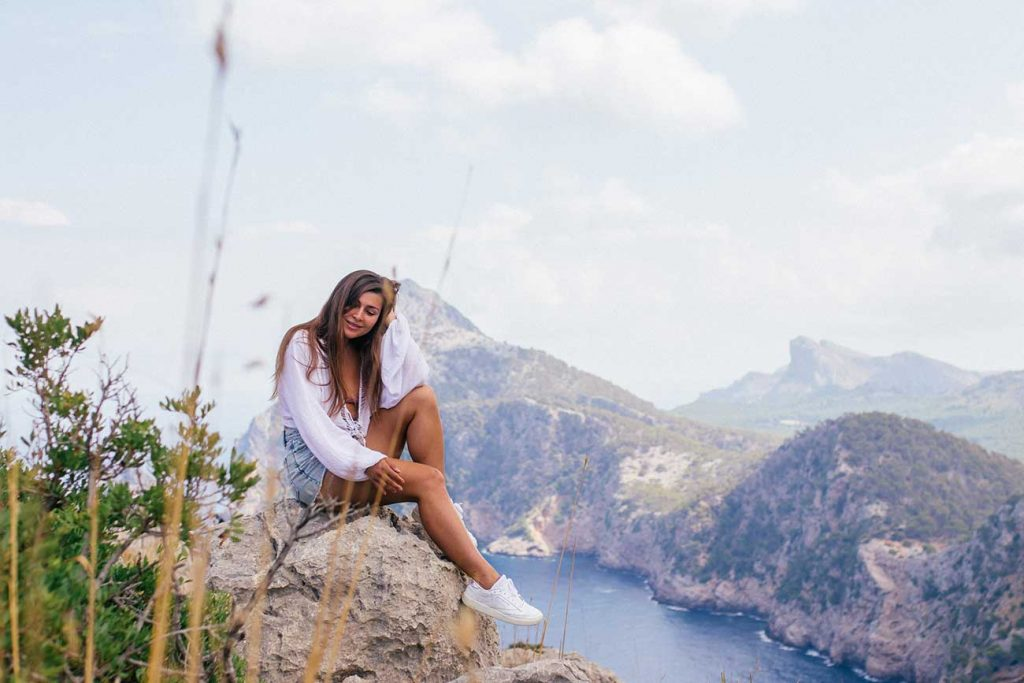 Melissa sitting on a rock with a view over the Cap de Formentor