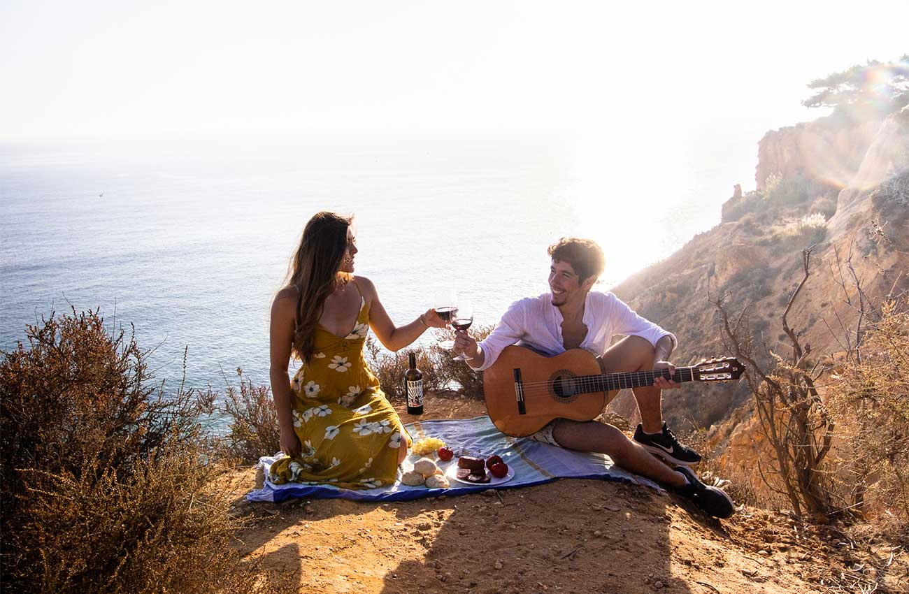 Melissa and Guga on a seaside hill in Lagos, one of the best things to do in Lagos Portugal