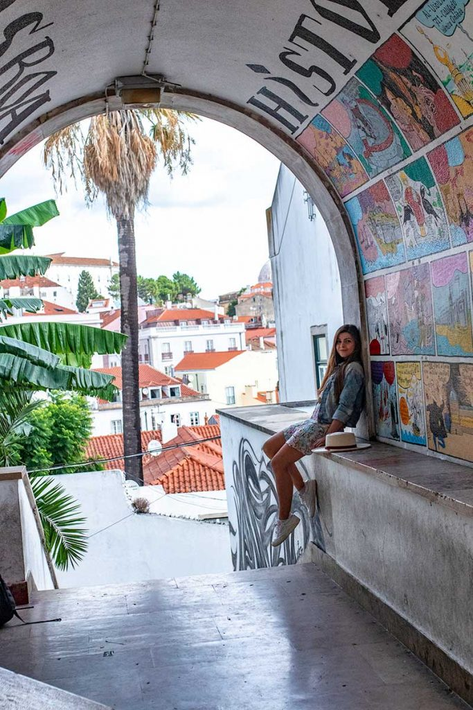 Melissa sits in a tunnel filled with street art in the Alfama District of Lisbon
