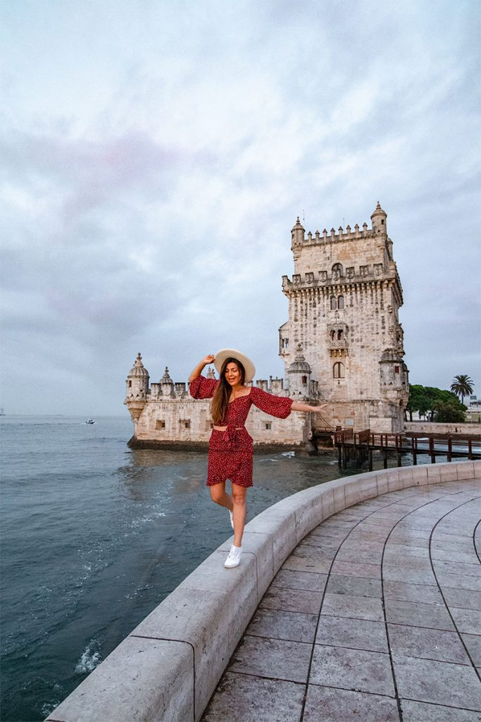 Melissa balances on a low wall outside Belem Tower in Lisbon Portugal