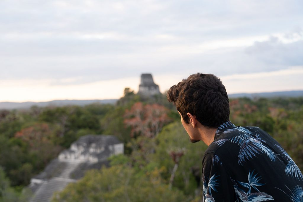 Guga standing over the Tikal Ruins at sunset