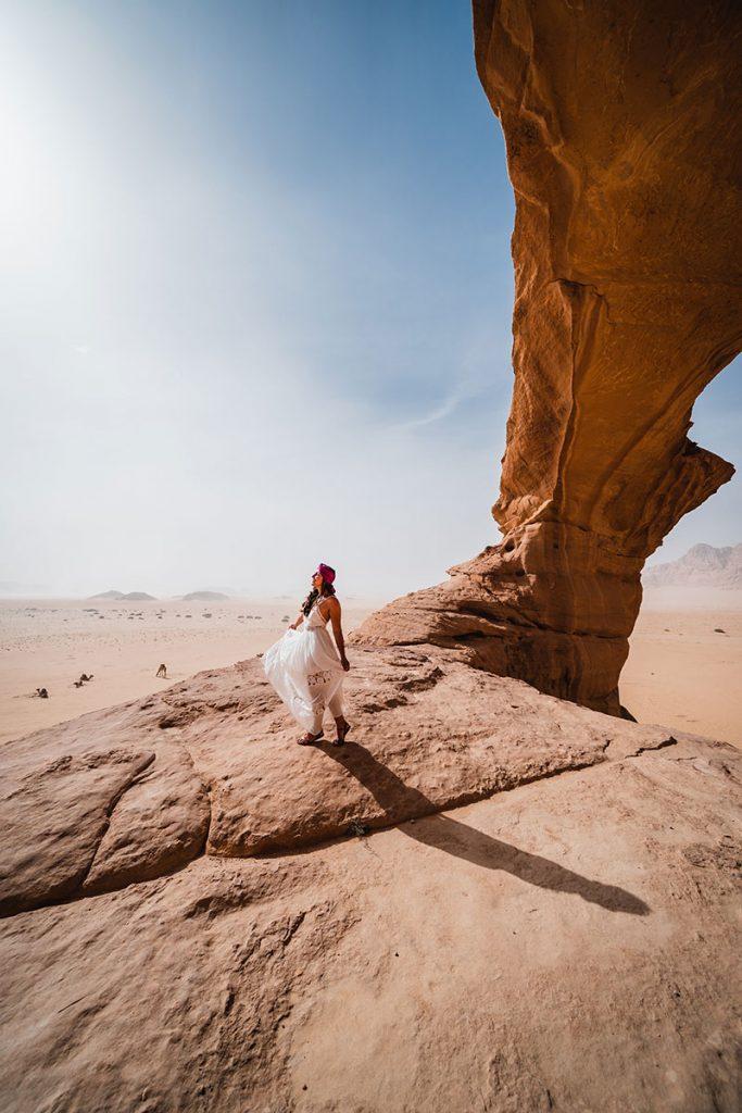 Melissa standing under the rock bridge on the Wadi Rum Desert