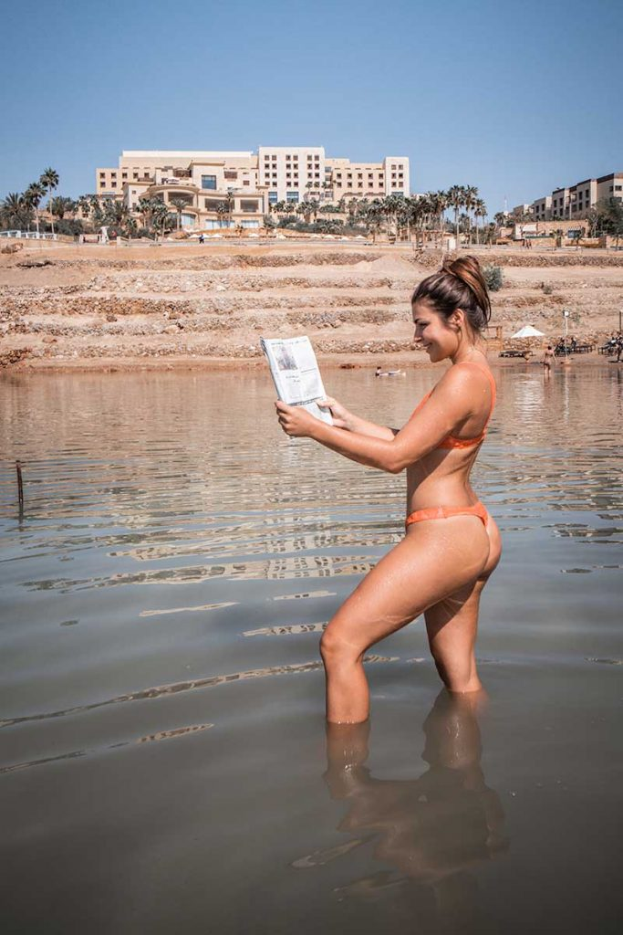 Melissa pretends to reads an Arabic newspaper as she stands in the shallows of the Dead Sea.