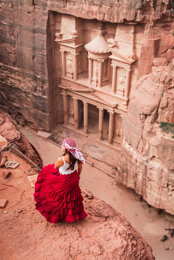 Melissa standing on the edge of a cliff overlooking the Treasury in Petra Jordan