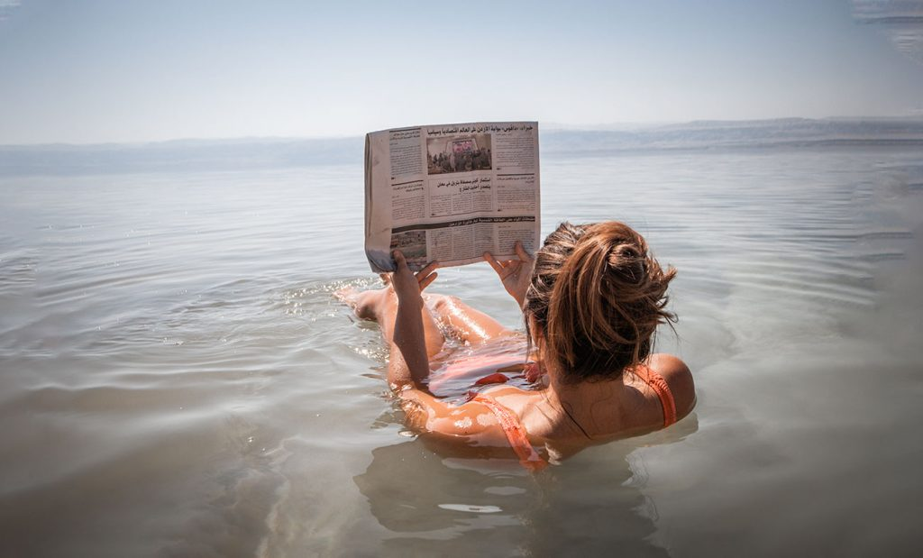 Melissa reads an newspaper upside down while bathing in the dead sea