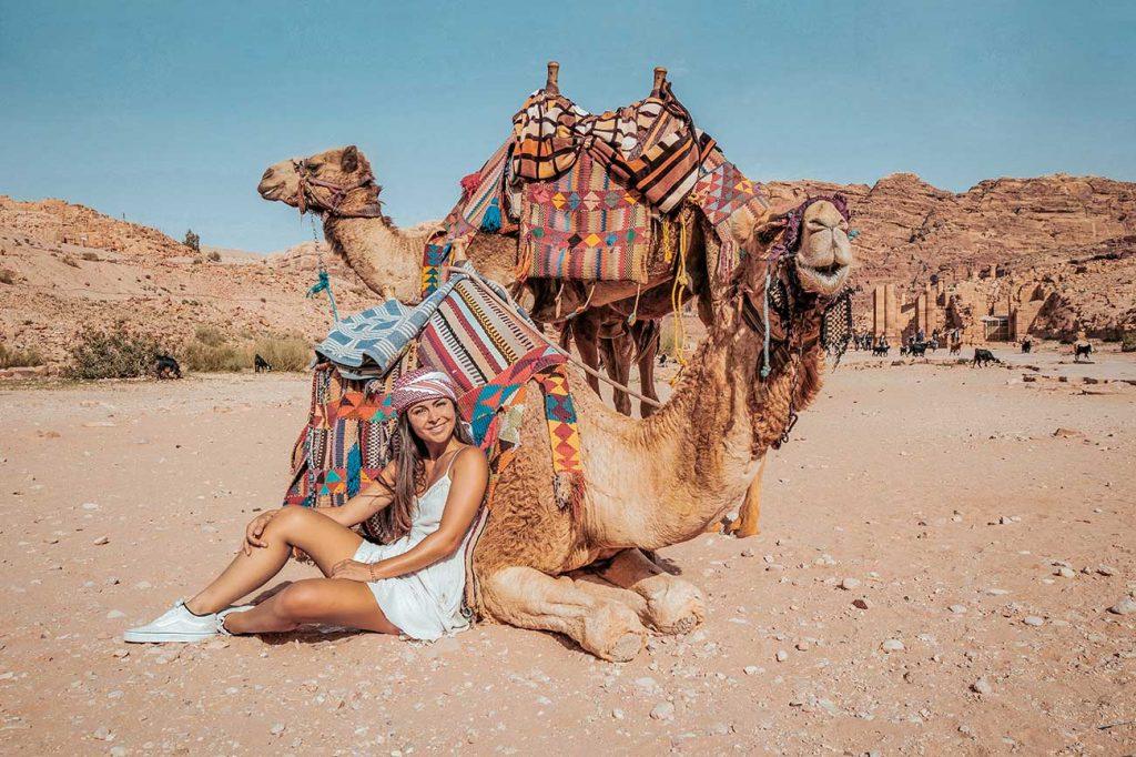 Melissa sitting in front of a camel in Jordan