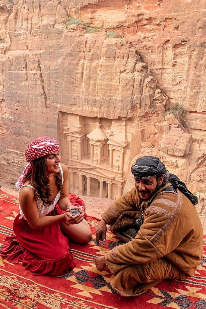 Melissa sitting with a bedouin overlooking the treasury in Petra Jordan