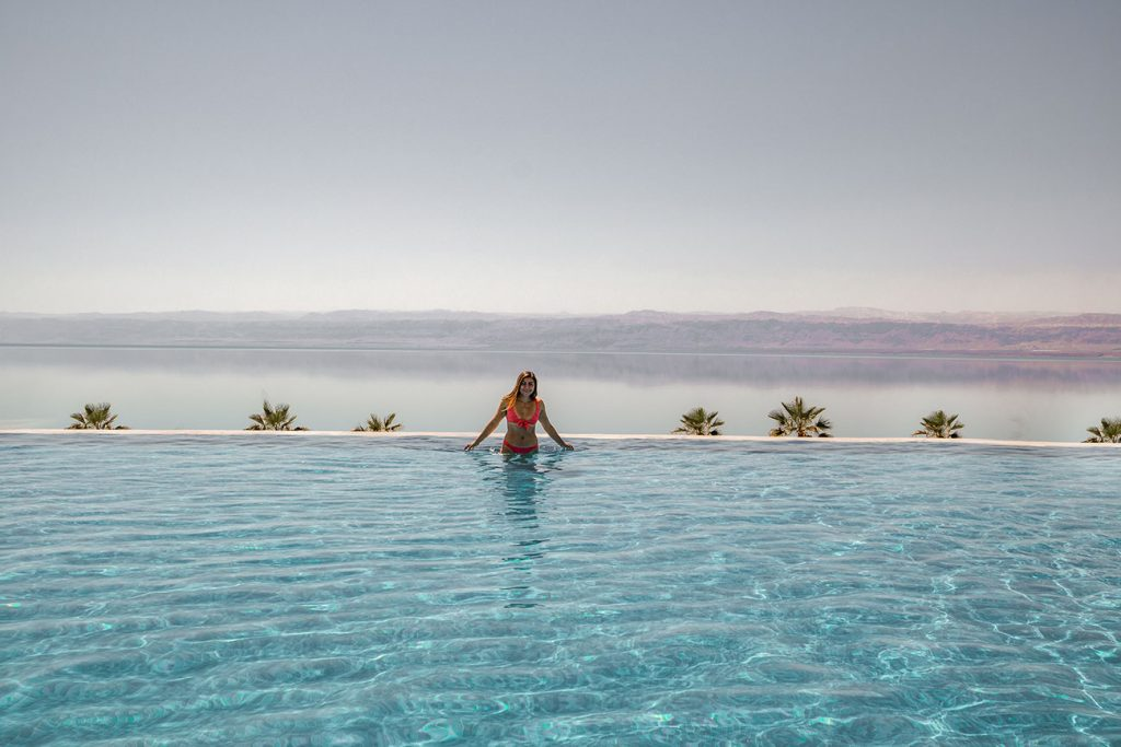 Melissa stands in the infinity pool at the Kempinski Hotel, the dead sea spans the horizon behind her.