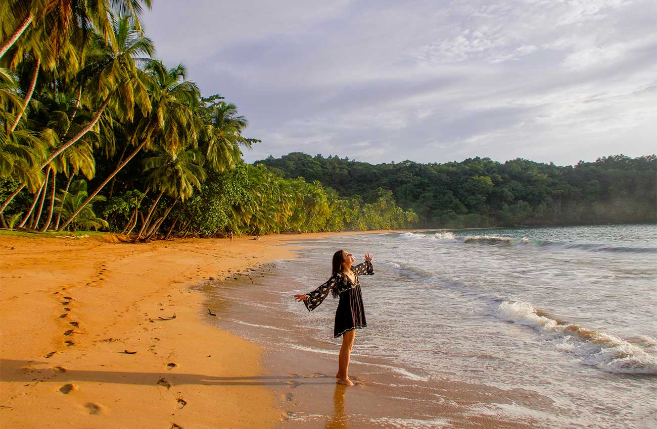 Melissa standing with her arms open wearing a dress on a remote beach in Sao Tome and Principe