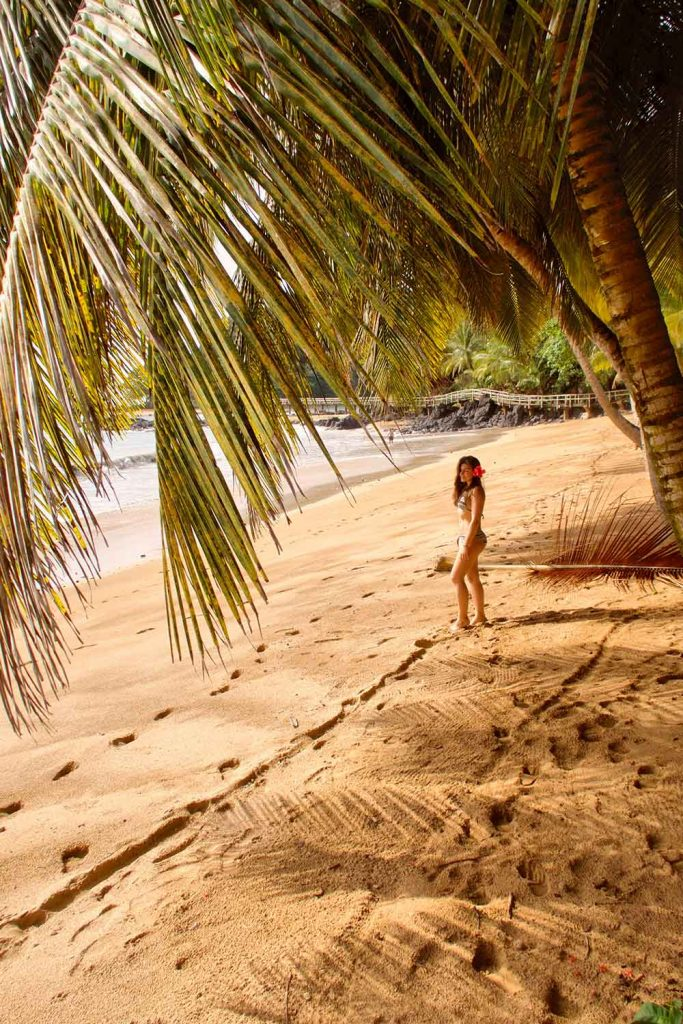 melissa standing under a palm tree in bom bom beach in principe
