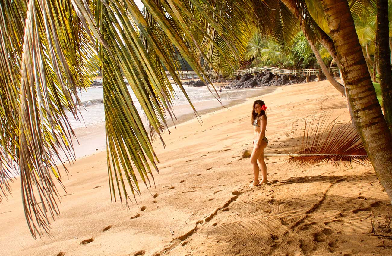 Melissa standing under a palm tree at a paradisiac beach in Sao Tome and Principe