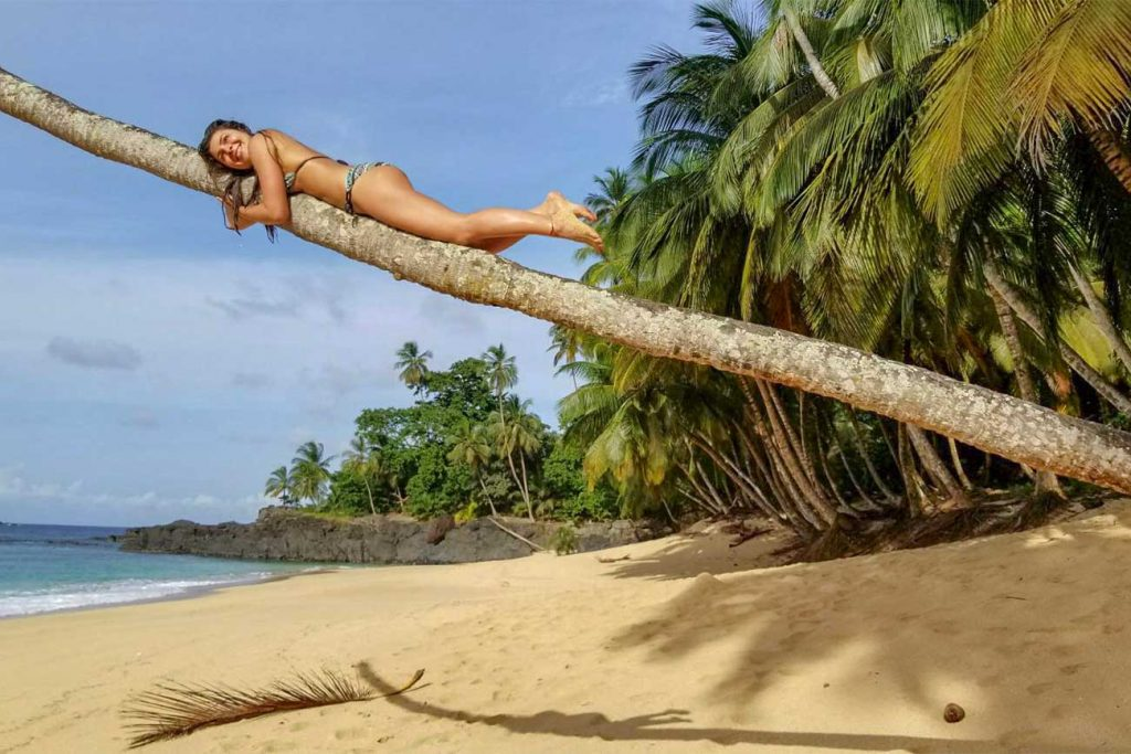 melissa holding onto a palm tree at bom bom beach in sao tome and principe