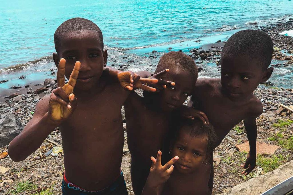 four local kids making a peace sign with their hands in sao tome and principe