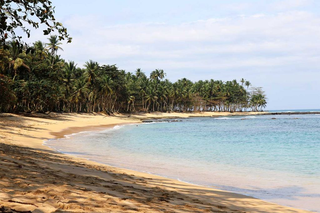 sand and sea surrounded by palm trres at Praia Jale in Sao Tome