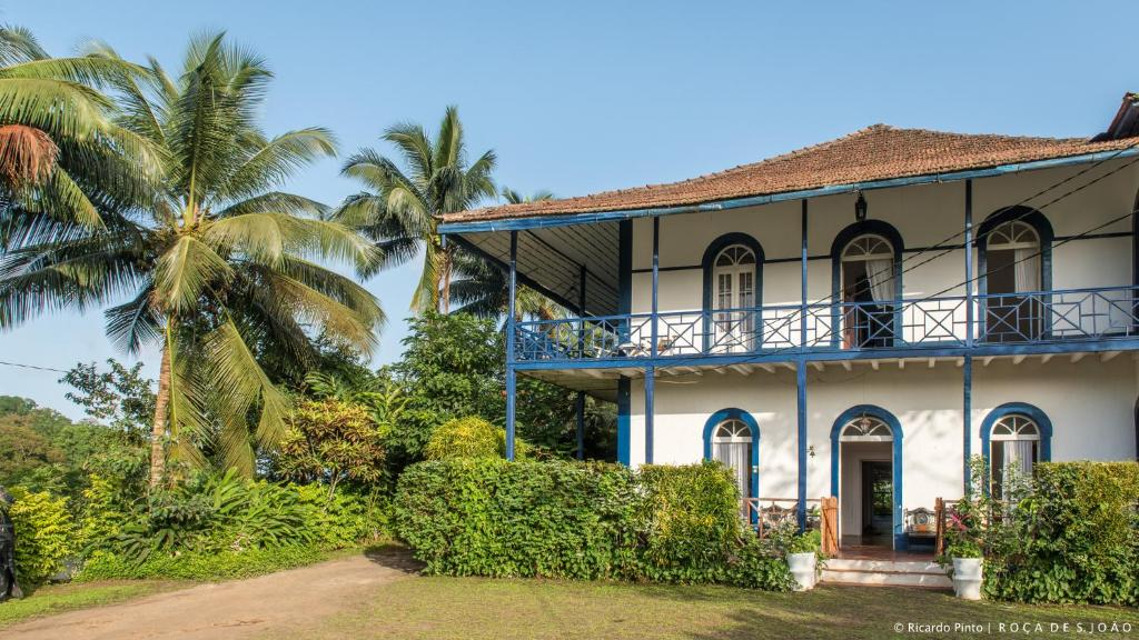 Main house next to tall palm trees at Roça São João dos Angolares in Sao Tome