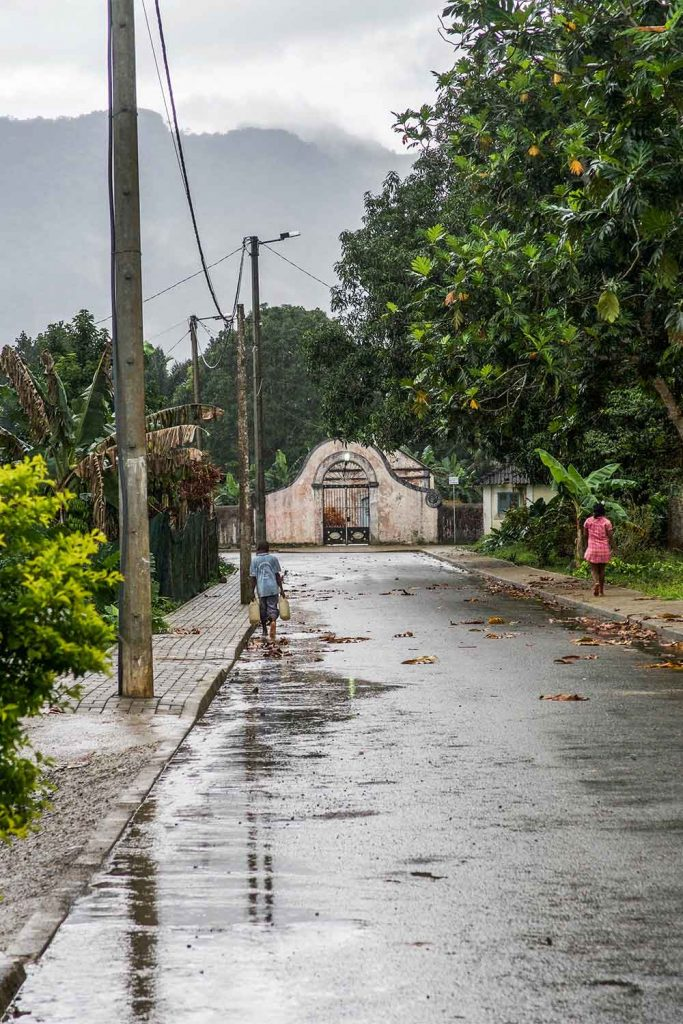 person walking down the rainy street in sao tome