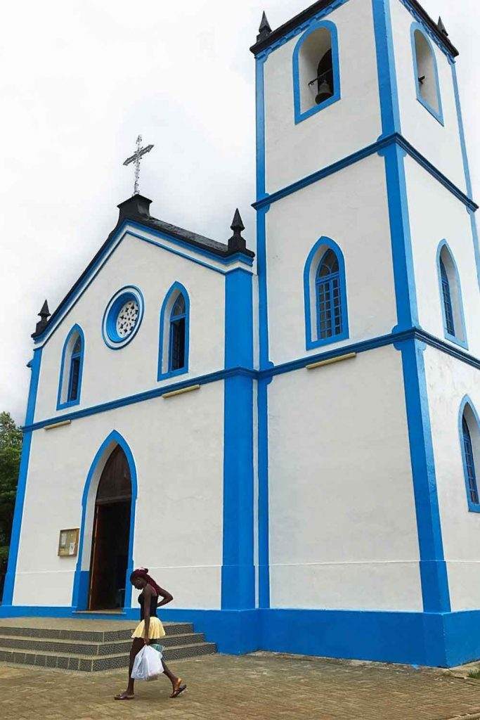 person carrying groceries in front of a church in sao tome town