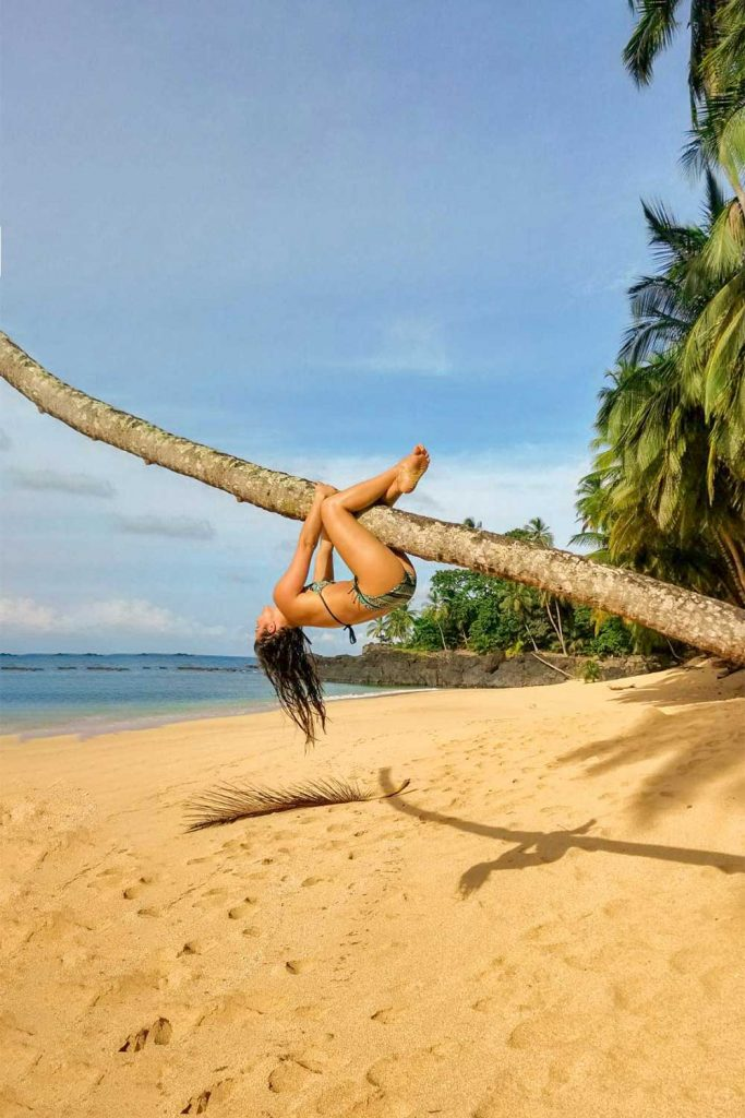 Melissa upside down holding onto a palm tree at the beach