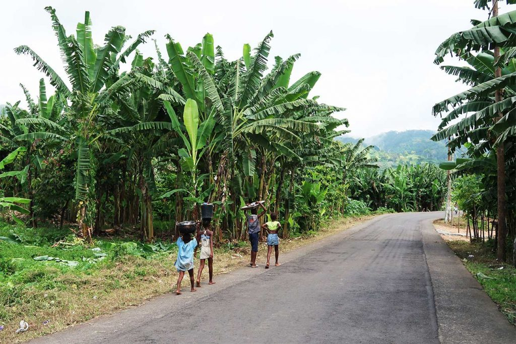 locals walking down an empty street in sao tome and principe