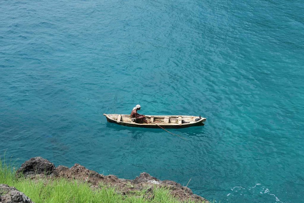 person paddling a canoe next to the mangroves in sao tome